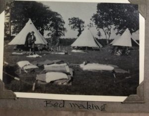 Photo of bed making in front of bell tents from 1929