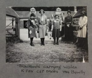 Photo of girls carrying water buckets at 1929 camp