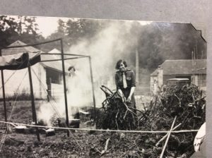 Photo of girl managing cooking fire at 1929 camp