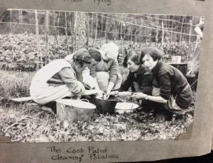 Photo of gils washing items in tin buckets at 1029 camp
